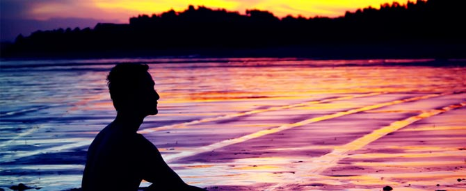 silhouette of man sitting by water