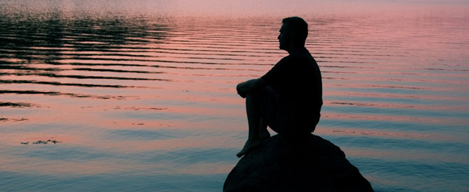 Silhouette of man sitting on a rock contemplating life.