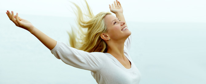 Happy, blonde woman with arms outstretched and looking up.