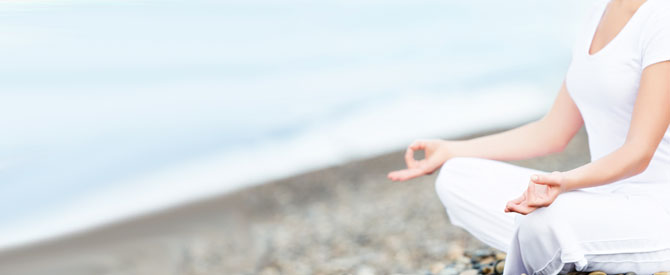 woman in white meditating on the beach