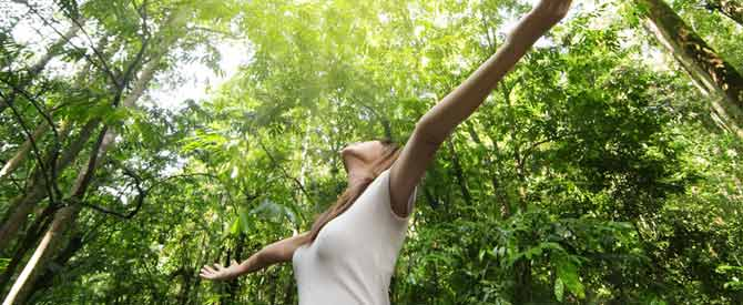 woman with arms outstretched standing amidst a circle of trees